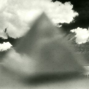 out-of focus triangle shape in foreground; large white clouds floating in dark sky