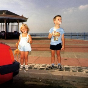 two children standing on curb holding melting ice cream cones with ice cream on their faces; ocean and lighthouse in the background