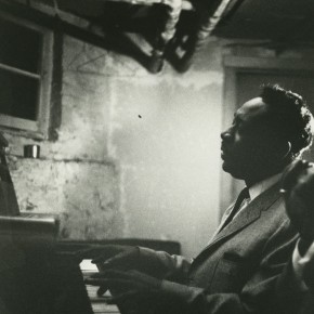 portrait of Otis Spann playing piano in a dingy room