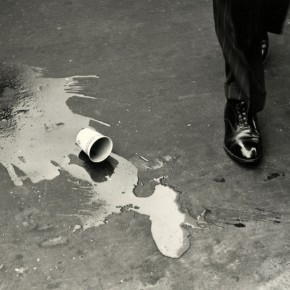 spilled coffee cup on street next to man's foot