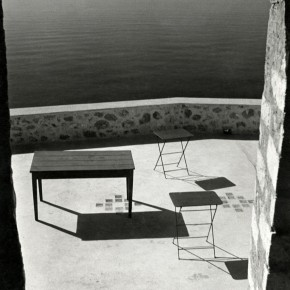 still-life with table and two chairs next to ocean in Greece