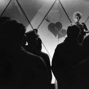 woman dancing on stage; figures of men watching