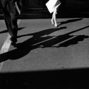 lower halves of man and woman walking across street and casting their shadows