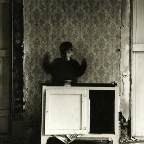 child in motion with hands raised, standing behind cabinet in decaying house