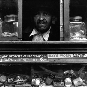 merchant in harlem stares out of small, open window in front of his store