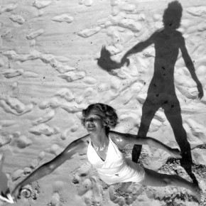 semi-aerial view of woman standing on beach, holding out a handkerchief with her shadow behind her