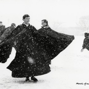 priests wearing long black coats spinning in the snow