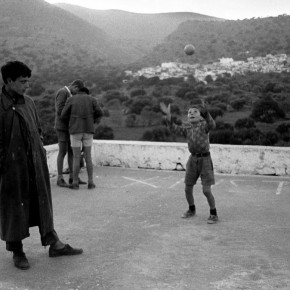 group of boys playing in the square in front of mountains in Crete