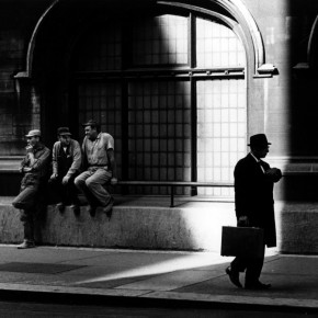 business man walking down street past three men in worker uniforms