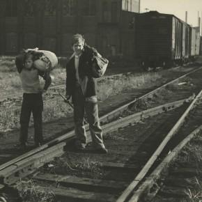 two boys standing on railroad tracks, holding knapsacks
