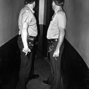 two police officers facing each other while looking towards two doors at the end of a narrow corridor; one officer holds a gun and the other holds a cigar