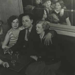 man with two women on either side of him at a bar; people sitting across from them are reflected in mirror