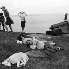 people sleeping, sitting and standing on grass next to body of water; child sits on cannon